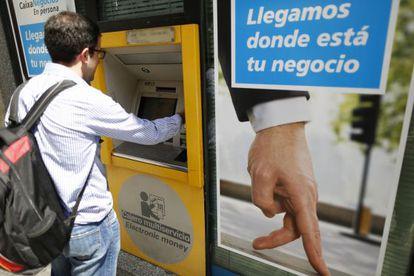 Un ciudadano utiliza un cajero automático de CaixaBank en Madrid. Samuel Sanchez