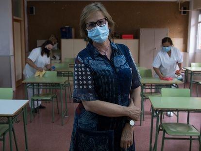 Mariam González, directora del IES Juan de Mairena, en San Sebastián de los Reyes, posa en un aula mientras el personal de limpieza realiza labores de higienización.
