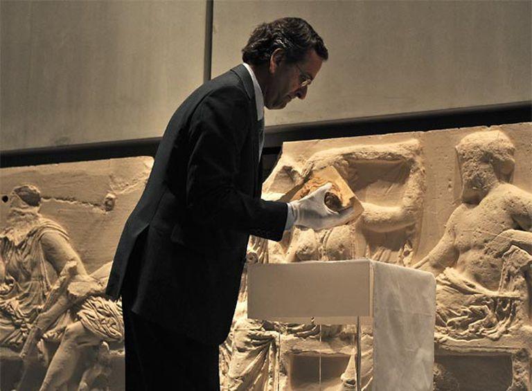 El ministro de Cultura griego, Antoni Samaras, ayer con la pieza original del Partenón que ha devuelto el Vaticano.
