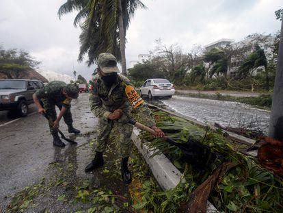 Miembros del Ejército quitan los restos de árboles caídos tras el paso del huracán Delta por Cancún.