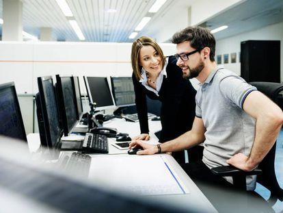 Empleados de una compañía ante el ordenador con el que trabajan cada día.