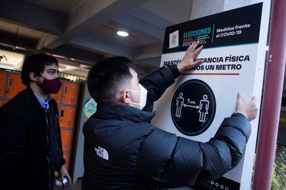 Dos trabajadores del Servicio Electoral de Chile (Servel) instalan carteles de orientación para electores en el Colegio Providencia, uno de los centros habilitados para las elecciones del 15 y 16 de mayo.
