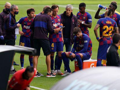 Quique Setién y su segundo entrenador, Eder Sarabia, dan indicaciones a sus jugadores durante el receso para hidratación.