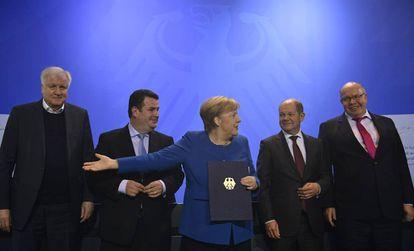 La canciller alemana, Angela Merkel, muestra el documento que permitirá acelerar la entrada de trabajadores cualificados en Alemania, este lunes en Berlín.