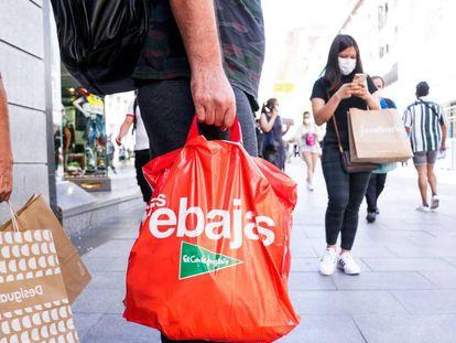 Varias personas caminan por el centro de Madrid con bolsas de compras en varios establecimientos de la capital.