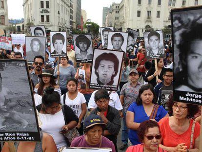 Manifestantes portan imágenes de las víctimas de los crímenes por los que fue condenado.