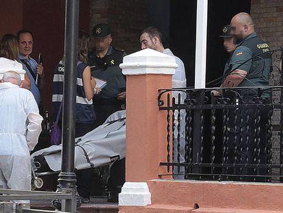 Empleados del servicio funerario trasladan el cadáver de uno de los dos muertos en el incendio de un bar en Lanjarón.
