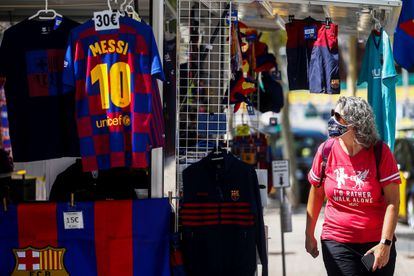 Una persona mira una camiseta de Leo Messi en una tienda cercana a las instalaciones del Camp Nou.