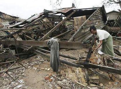 Un hombre intenta recoger entre los escombros de su casa.