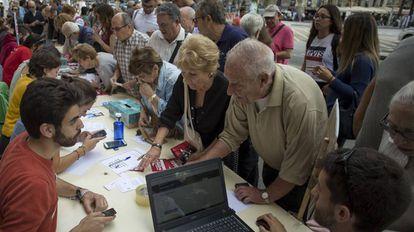 Varios jóvenes universitarios informan del lugar donde votar el próximo domingo, en el referéndum ilegal del 1-O, en Barcelona.
