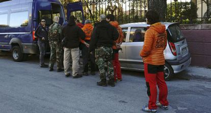 Los agentes griegos conducen esposados a los españoles, el jueves.