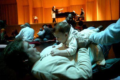 Un padre juega con su bebé en un concierto en Barcelona.