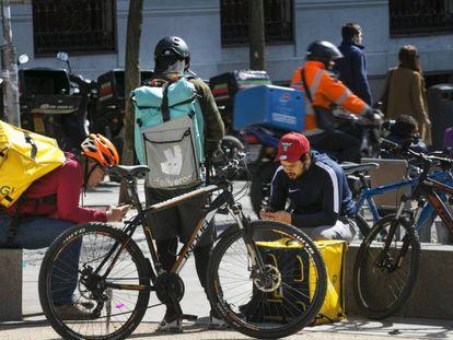 Trabajadores de Deliveroo y Glovo en la plaza de Alonso Martínez, en Madrid.
