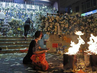 Una mujer quema dinero en señal de respeto a los manifestantes que resultaron heridos frente a la estación Prince Edward, este viernes en Hong Kong.
