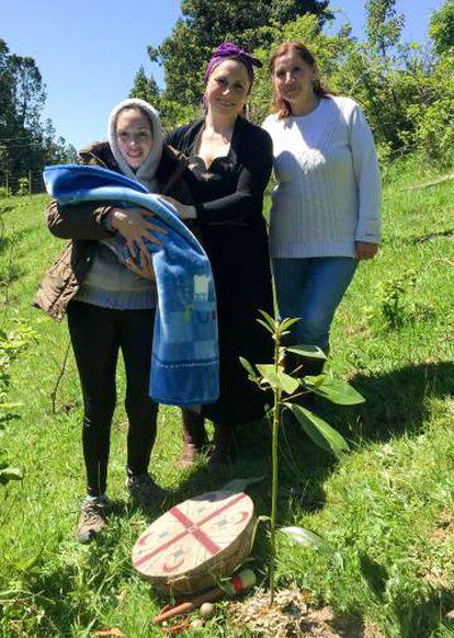 Yoana Aron junto con dos miembros de la comunidad huilliche tras la celebración en la que se plantó la placenta junto con un pequeño árbol.