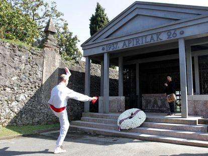 Un 'dantzari' baila frente a la corona de flores depositada en recordatorio a las víctimas del bombardeo de 1937.