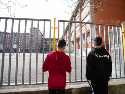 Dos adolescentes observan el patio cerrado de un colegio de Vitoria durante el confinamiento