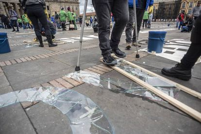 Un activista escribe en vidrio fracturado el nombre de un líder asesinado.
