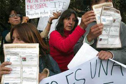Simpatizantes del candidato a la presidencia de México por la coalición 'Por el bien de todos', Andrés Manuel López Obrador, sostienen boletas electorales que encontraron en un vertedero de basura.