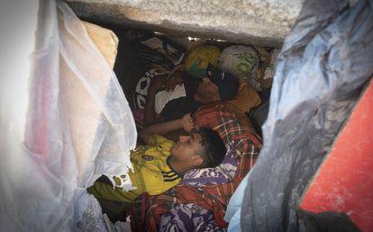 Dos migrantes duermen en el hueco de uno de los bloques de hormigón de la escollera.