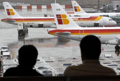 Dos pasajeros observan varios aviones de la compañia Iberia