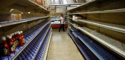 Una mujer ante los estantes casi vacíos de un supermercado en Caracas el viernes.