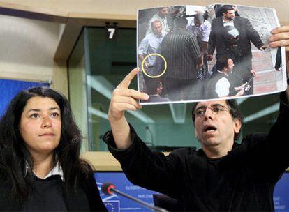 El director de cine iraní Molsen Makbalmaf, acompañado por Marjane Satrapi, muestra en Bruselas una fotografía de milicianos armados.