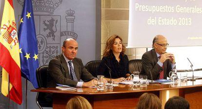 Guindos (izquierda) presenta el programa de reformas en septiembre junto a Soraya Sáenz de Santamaría y Cristóbal Montoro.