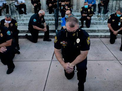 Agentes de policía se arrodillan durante la manifestación en Coral Gables (Florida).