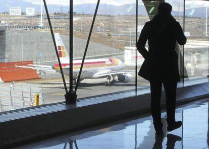 Un pasajero observa un avión de Iberia en el aeropuerto de Madrid-Barajas