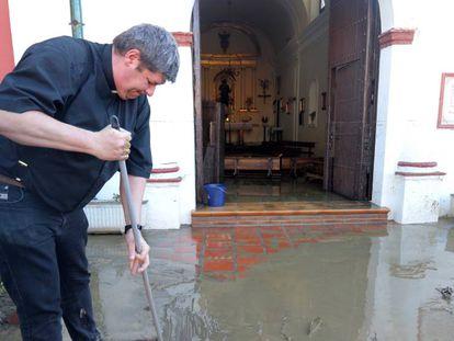 El párraco Eduardo Romero limpia los destrozos de las inundaciones.