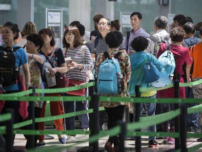 Pasajeros aguardando en la cola de los controles del aeropuerto del Prat, este martes.