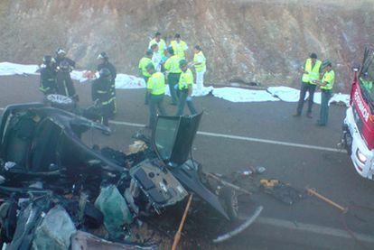 Guardias civiles, bomberos y personal sanitario, junto al amasijo de hierros en que quedaron los vehículos. Detrás, varios de los cadáveres.