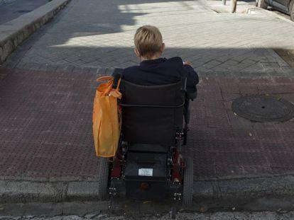 Una mujer en silla de ruedas sube un bordillo en una calle de Madrid.