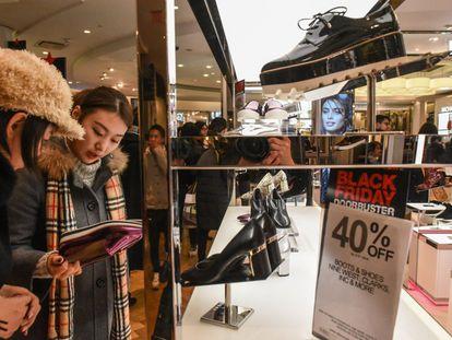 Unas jóvenes observan unos zapatos en una tienda de Nueva York (Estados Unidos).