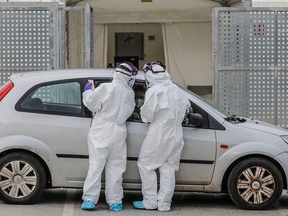 Dos sanitarios realizan una prueba PCR a una persona desde su vehículo a las puertas del Hospital de Campaña próximo al de La Fe, en Valencia (España), el lunes 25 de enero.