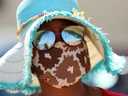 Una mujer con mascarilla acude a por comida que están repartiendo las autoridades en Sudáfrica.
