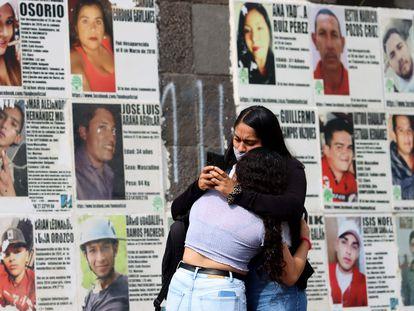 Dos mujeres se abrazan delante de imágenes de personas desaparecidas, en Guadalajara, Jalisco, este domingo.