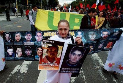 Una mujer sostiene dos fotografías de desaparecidos durante una marcha por las calles del centro de Bogotá (Colombia).