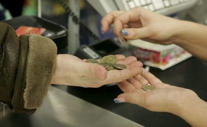 Una cajera ayuda a un cliente a contar las monedas de euro en un supermercado.
