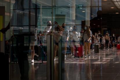 Varios pasajeros llegan al aeropuerto del Prat de Barcelona, este lunes.