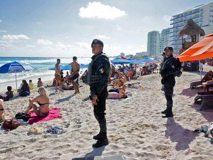 Policías federales vigilan una plata de Cancún este enero.
