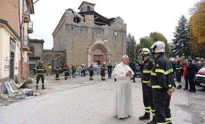 El Papa conversa con unos bomberos, este martes frente a una iglesia destruida por el terremoto en Amatrice (Italia).