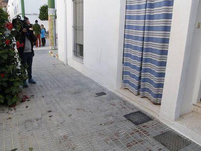 Un camarógrafo de televisión toma imágenes de la vivienda donde fue asesinado a tiros una mujer en Sanlúcar la Mayor.