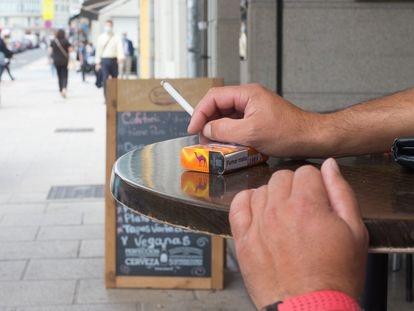 Una persona fuma en una terraza durante el primer día de la prohibición en Galicia.