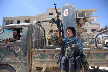 Um Alí posa con su arma en el centro del poblado sirio Al Qariaten tras combatir y expulsar de la aldea al ISIS.