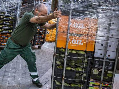 Un trabajador abastece un supermercado en Barcelona durante los primeros días del estado de alarma por el coronavirus.