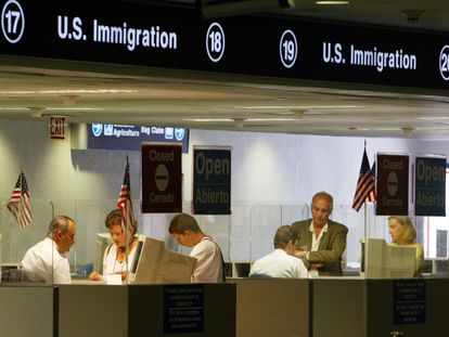 Inspectores de migración revisan pasaportes en el Aeropuerto de Miami.