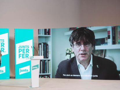 La candidata a la presidencia de la Generalitat, Laura Borràs, atiende la intervención telemática del expresident de la Generalitat Carles Puigdemont en el acto de inicio de campaña de JxCat.