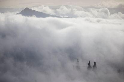 Vista de las torres de la catedral de Santiago entre la niebla, con el monte Pico Sacro al fondo.